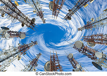 Mobile phone communication antenna tower with cloud and blue sky.