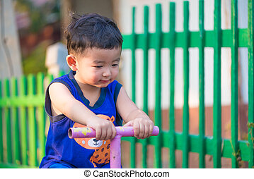 Asian kid riding seesaw board at the playground. - Asian kid...