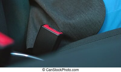 Female hand fastening car safety seat belt while sitting...