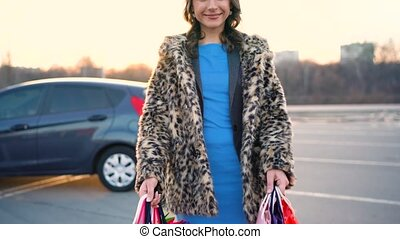 Smiling Caucasian woman putting her shopping bags into the...