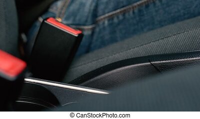 Male hand fastening car safety seat belt while sitting...