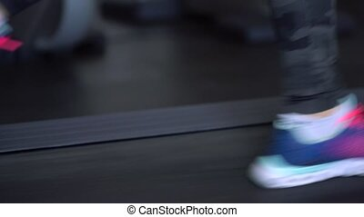 Woman running on treadmill in gym - Young woman running on...