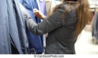 Woman choosing items during shopping at clothing shop