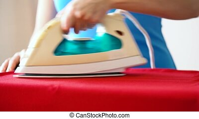 Caucasian woman ironing some clothes