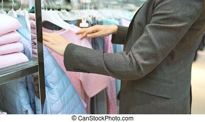 Woman choosing items during shopping at clothing shop -...