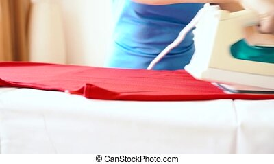 Caucasian woman ironing some clothes - Caucasian woman...