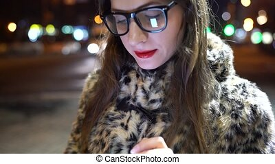 Young woman in glasses using smartphone on night city lights background