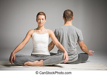 Couple sitting in lotus position - Young couple practicing...