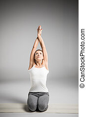 Woman sitting in yoga position - Woman practicing yoga...