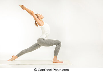 Woman standing in yoga position - Woman practicing yoga...