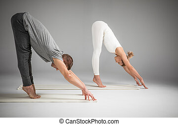 Couple practicing yoga - Side view of couple practicing yoga...