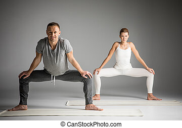 Couple practicing yoga doing Sumo Squat Pose