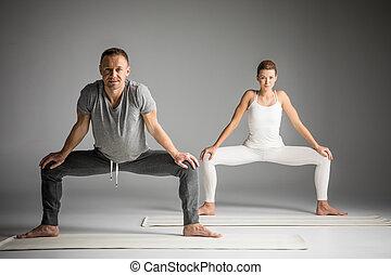 Couple practicing yoga doing Sumo Squat Pose