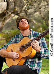 Hipster man playing a guitar in the field