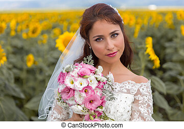 Closeup of a bride in a sunflower field - Beautiful young...