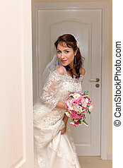 Peek a boo bride - Lovely young bride entering the room in...