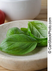 Whole Basil Leaves in close with Tomato in Background