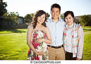 Asian family - A portrait of a pregnant asian woman with her...