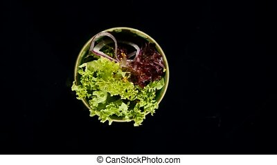Fresh green salad in a green dish on black background