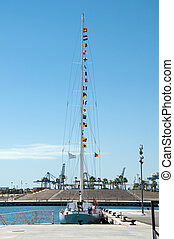Yacht with Morse code flags on mast moored to the pear