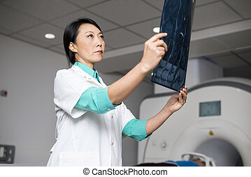 Doctor Examining X-ray While Patient Lying On CT Scan Machine