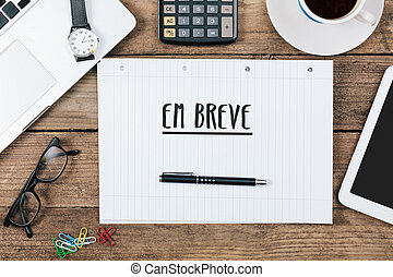 Em breve, Portuguese text for Coming Soon on note pad at office desk with computer technology, high angle