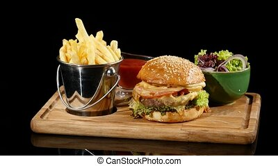 Rotating hamburger with ketchup poured over french fries and...
