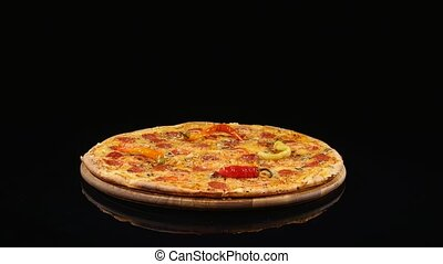 pizza spinning with tomato circles, isolated over black.