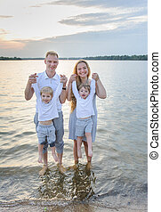 Happy family - father, mother, two sons on the beach with their feet in the water at sunset