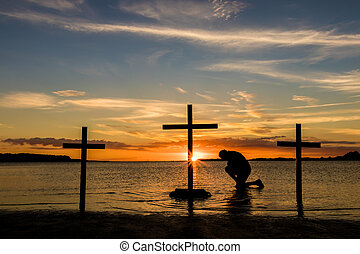 Calvary Prayer - Man kneeling ion prayer at three crosses at...