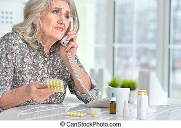 Sick elderly woman calling a doctor