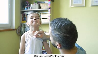Little girl with chickenpox, father applying antiseptic...