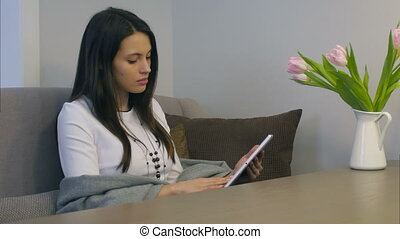 Young woman using electronic tablet sitting on sofa with flowers on the table