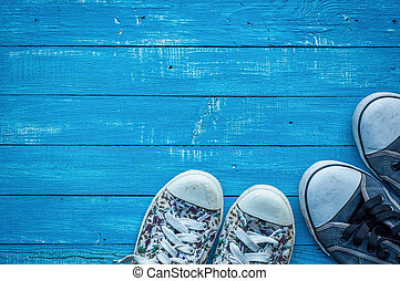 pair of female and male worn sneakers on a wooden board
