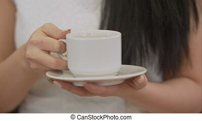 Female hand holding cup of black coffee. Close up....