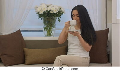Young brunette sitting on sofa drinking tea from cup in a office