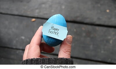 Happy easter. Hand holding an egg with tag.