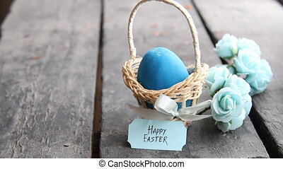 Happy easter. Blue egg on rustic table and a basket with a tag. Copy space.