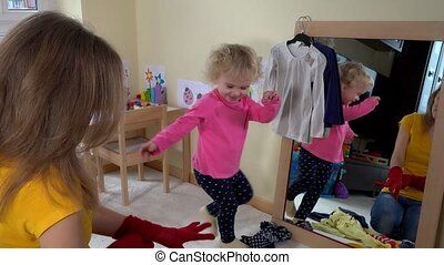 Loving mother playing with her toddler daughter girl near mirror