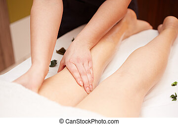 Detail of hands massaging human calf muscle.Therapist applying pressure on female leg
