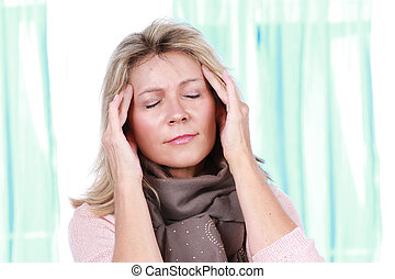 Mature woman with headache holds her hands at her forehead