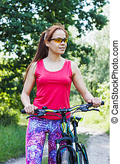 Sports woman with a bike on the walk - Young woman in the...