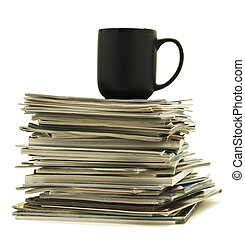 Coffee mug sitting on magazine pile - Black coffee mug sits...