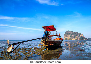 Boat stand on the beach during low tide with blue sky