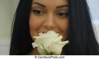 Young woman smells white rose and smiles. Close up....