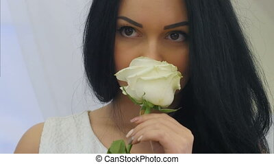 Young pretty woman smelling white rose flower and dreaming....