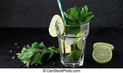 Pouring in glass Iced green tea with lime, lemon and mint on...