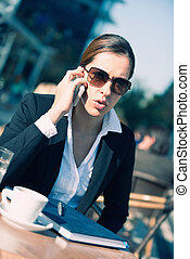 Young business woman on the phone, having cofee outdoors
