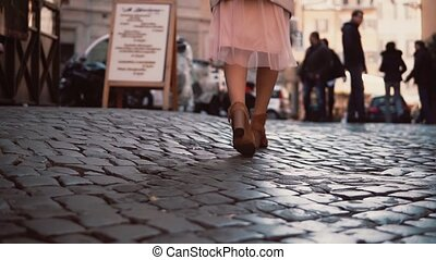 Woman walking on cobblestone pavement road in city. Girl...