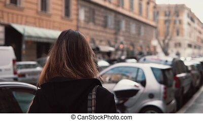 Back view of young woman walking in the city centre and looking around. Brunette girl with backpack explores new place.